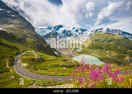 Beautiful view of winding mountain pass road in the Alps running through idyllic alpine scenery with mountain peaks, - Stock Photo