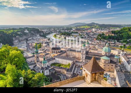 Aerial panoramic view of the historic city of Salzburg with Salzach river in beautiful golden evening light with - Stock Photo