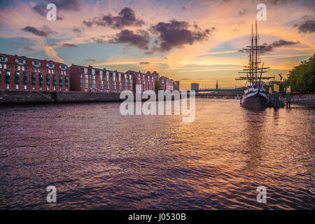 Panorama view of the historic city center of Bremen with an old sail ship on Weser river in beautiful golden evening - Stock Photo