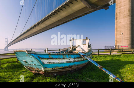 A derelict wooden boat under the Humber Bridge which spans the Humber estuary and viewed on a spring morning in - Stock Photo