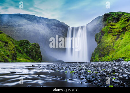 Classic long exposure view of famous Skogafoss waterfall in beautiful twilight during blue hour at dusk in summer, - Stock Photo