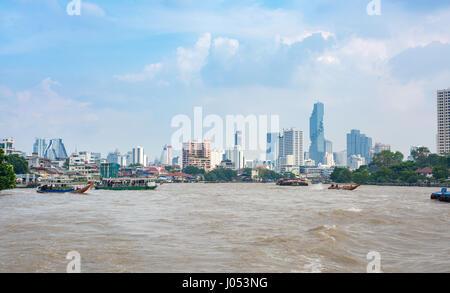 BANGKOK, THAILAND - OCTOBER 14, 2016: Bangkok cityscape from the busy Chao Phraya River with many boats full of - Stock Photo