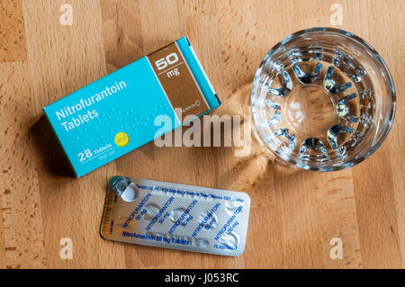 A packet of Nitrofurantoin tablets used for the treatment of bladder infections on a bedside table with a glass - Stock Photo