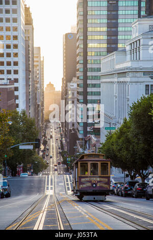 Classic view of historic Cable Car riding on famous California Street in beautiful golden morning light at sunrise - Stock Photo