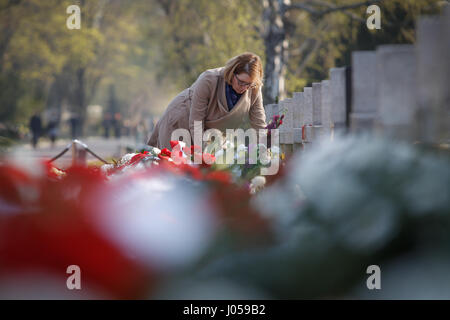 Warsaw, Poland. 10th Apr, 2017. A woman lays flowers to a tombstone at the Warsaw Powazki Military Cemetery in Warsaw, - Stock Photo