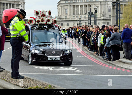 London, UK. 10th Apr, 2017. A police officer bows her head as the funeral cortege of PC Keith Palmer passes over - Stock Photo
