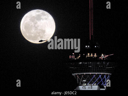 Las Vegas, Nevada, USA. 25th Apr, 2013. A helicopter flies by a full moon as it rises behind the Stratosphere Tower - Stock Photo