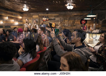 Man in audience using camera phone at music concert - Stock Photo