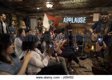Audience with camera phones photographing musician playing guitar and singing on garage stage - Stock Photo