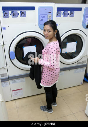 young woman doing laundry in the laundry room - Stock Photo