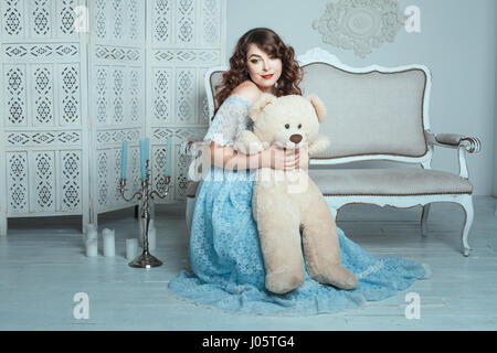 Plump woman hugging bear toy, she sits on the floor in the room. - Stock Photo