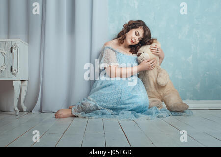 Plump woman sitting on the floor in the room, she gently hugging bear toy. - Stock Photo