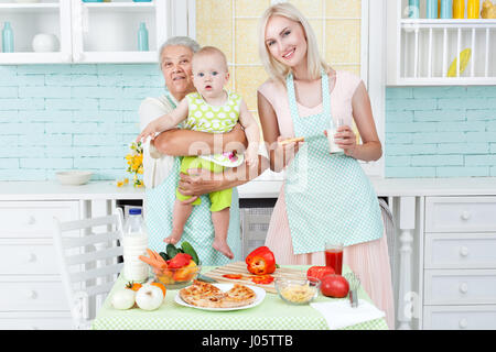 The grandmother the young girl and the small child in kitchen near a table on which pizza lies. - Stock Photo