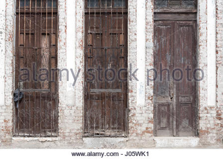 Cuban old weathered and worn out architecture. Typical facade of house. Results of economic hardship on real estate. - Stock Photo