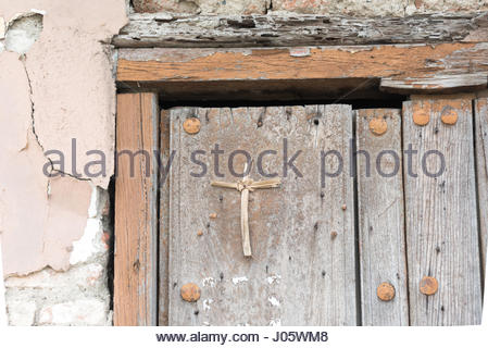 Cuban old weathered and worn out architecture. Christian cross in colonial door. Results of economic hardship on - Stock Photo