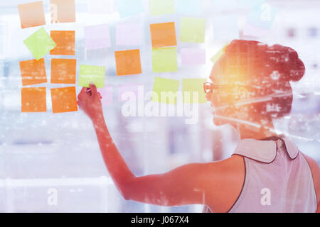 High angle view of illuminated cityscape against rear view of designer looking at sticky notes on glass - Stock Photo
