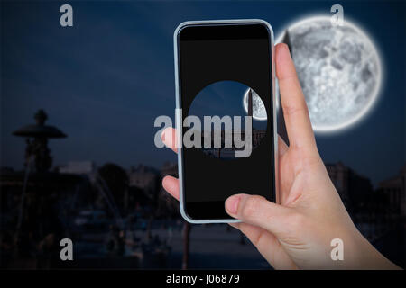 Human hand holding mobile phone against white background against large moon over city - Stock Photo