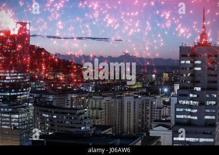 White fireworks exploding on black background against illuminated buildings in city against sky - Stock Photo
