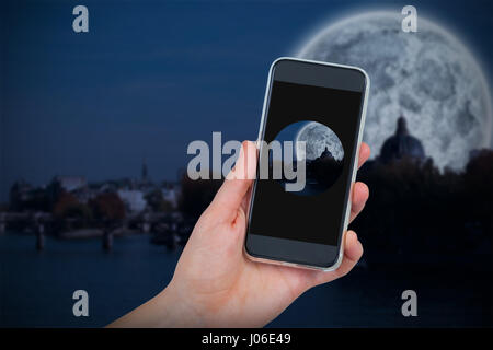 Hand holding mobile phone against white background against large moon over river city - Stock Photo