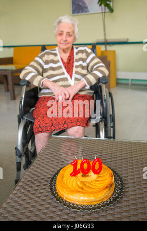 Old woman in a nursing home, on her one hundred birthday with her birthday's cake. - Stock Photo