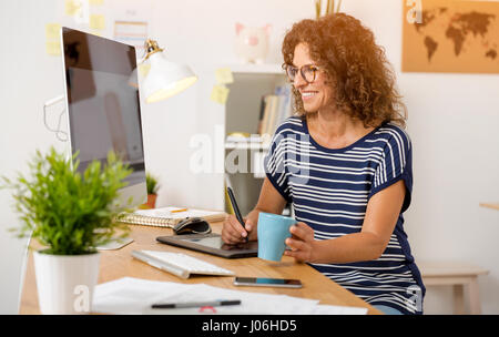 Middle age designer working on a desktop with a stylus pen - Stock Photo