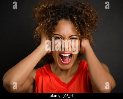 Portrait of an African American woman with hands on the head and yelling - Stock Photo