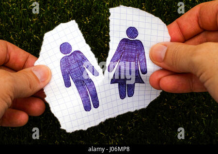 Person hands ripping piece of paper with hand drawn man and woman figures. Grass background. Doodle style. - Stock Photo