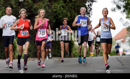Photomontage of Male and female athletes wearing running sports clothing pictured running in a half marathon road - Stock Photo