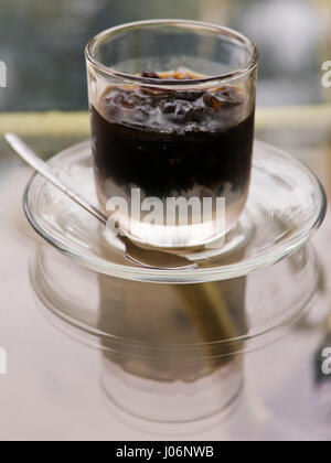 Vertical close up of an iced Vietnamese coffee in Vietnam. - Stock Photo