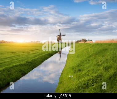 Windmills at sunrise. Rustic landscape with dutch windmills near the water canals, green grass and blue cloudy sky - Stock Photo
