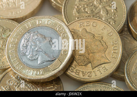 The new 12 sided British Pound Coin on top of the older round coins - Stock Photo
