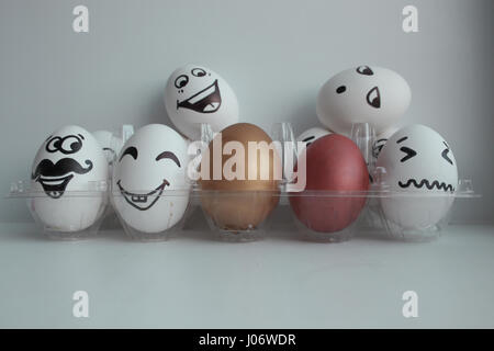 Eggs Easter white group in a transparent box with cheerful and mischievous faces having fun and standing on the - Stock Photo