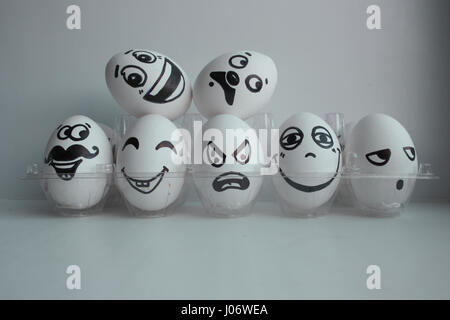 Eggs Easter white group in a transparent box with cheerful and mischievous faces have fun and stand on the heads - Stock Photo