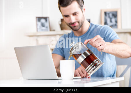 Young smiling man pouring tea in white cup while using laptop - Stock Photo