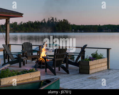 Adirondack Chairs And Campfire On A Dock, Lake Of The Woods, Ontario, Canada