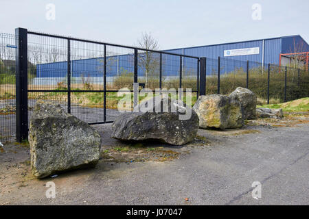 large boulders placed in front of derelict commercial plot to combat travellers squatting on site Newtownabbey UK - Stock Photo