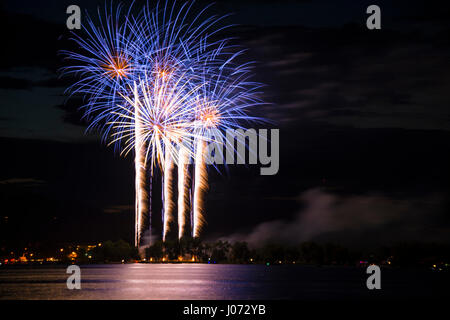 Fireworks celebration blue and gold reflecting in the lake - Stock Photo