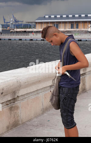 A young Cuban removes a hook from a fish on the waterfront along the Malecon in Old Havana, Cuba. - Stock Photo