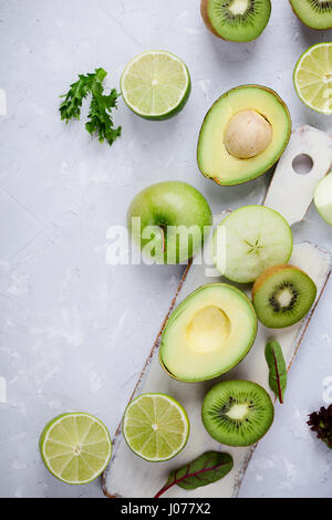 Frame of green vegetables and fruits white wooden cutting board over light gray plaster  table, food background - Stock Photo