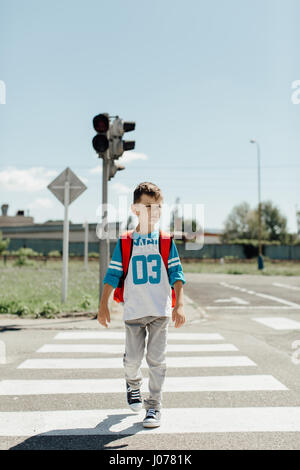 Schoolboy crossing a road on his morning way to school - Stock Photo
