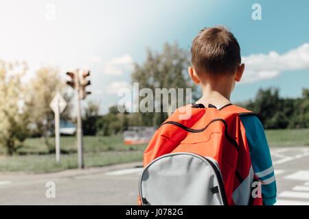 Schoolboy standing and waiting at zebra crossing - Stock Photo