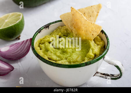 Guacamole with nachos avocado in Mexican molcajete in aged wood table ...