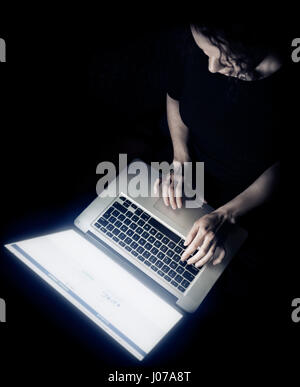 Overhead view of a young woman sitting with Apple Macbook laptop in front of her in darkness - Stock Photo
