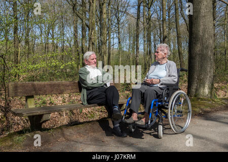 Disabled elderly woman in wheelchair talking to her retired husband sitting on a park bench during stroll in forest - Stock Photo