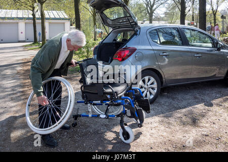 Senior man assembling / dismantling wheelchair from physically disabled elderly wife in front of car at parking - Stock Photo
