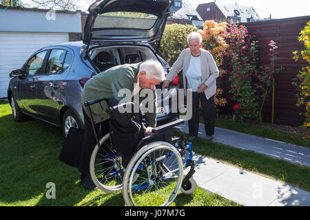 Senior husband assembling wheelchair from physically disabled elderly wife in front of car after returning at home - Stock Photo