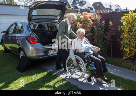 Senior husband taking physically disabled elderly wife for a ride in their car - Stock Photo