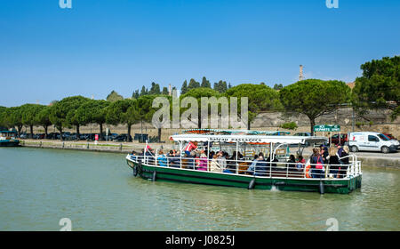 A boat full of tourists on the Canal du Midi in Carcassonne, France - Stock Photo