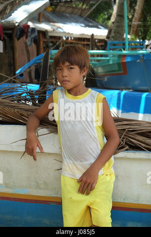 Portrait of a Filipino boy on the beach in El Nido leaning against a boat - Stock Photo