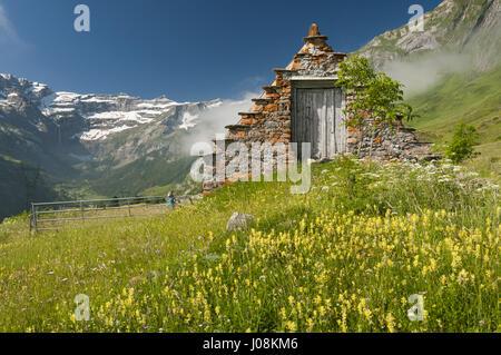France, Pyrenees, Saugue plateau, meadow landscape with Cirque de Gavarnie and farmhouse - Stock Photo
